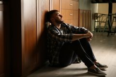 Deprimierter junger Mann, der auf Boden sitzt Stockbilder