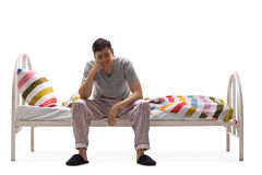 Deprimierter junger Mann, der auf einem Bett sitzt Stockfotos