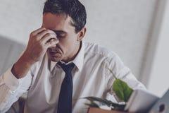 Deprimierter junger Mann, der die Brücke der Nase hält Lizenzfreie Stockfotografie
