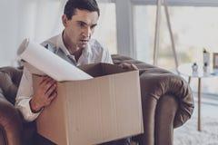 Deprimierter junger Mann, der einen Kasten hält Lizenzfreie Stockbilder