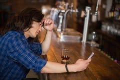 Deprimierter junger Mann, der Mobile an der Kneipe verwendet Lizenzfreie Stockbilder