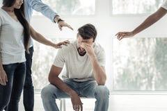 Deprimierter junger Mann, der seine Augen bedeckt Lizenzfreie Stockbilder