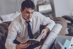 Deprimierter junger Mann, der seinen Planer betrachtet Lizenzfreies Stockbild