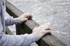 Deprimierter junger Mann, der Selbstmord auf Brücke über Fluss erwägt Stockbilder