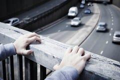 Deprimierter junger Mann, der Selbstmord auf Straßen-Brücke erwägt Stockfotografie