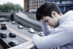 Deprimierter junger Mann, der Selbstmord auf Straßen-Brücke erwägt stockbilder
