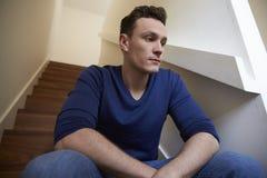 Deprimierter junger Mann, der zu Hause auf Treppe sitzt Lizenzfreie Stockfotografie