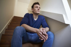 Deprimierter junger Mann, der zu Hause auf Treppe sitzt Lizenzfreie Stockbilder