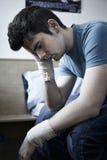 Deprimierter junger Mann mit den verbundenen Handgelenken nach Selbstmord-Versuch Stockbild