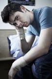 Deprimierter junger Mann mit den verbundenen Handgelenken nach Selbstmord-Versuch Lizenzfreie Stockfotos