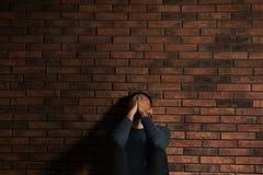 Deprimierter junger Mann nahe Backsteinmauer Stockbilder