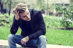 Deprimierter junger weißer Mann, der an der Straßen-Seite sitzt Stockfotos