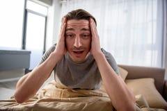 Deprimierter Kerl, der eine Migräne im Schlafzimmer hat Stockfotos
