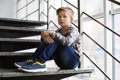 Deprimierter kleiner Junge, der zuhause auf Treppe sitzt Stockbild