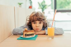 deprimierter kleiner Junge im Café mit Stück des Kuchens Lizenzfreie Stockfotos