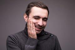 Deprimierter kranker Mann, der Zahnschmerzen und rührende Backe auf grauem Hintergrund hat Lizenzfreie Stockbilder