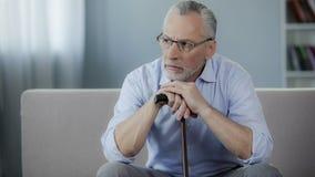 Deprimierter kranker Mann in seinem 50s, das auf der Couch, Hände auf Spazierstock setzend sitzt Lizenzfreie Stockbilder