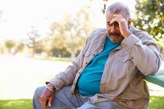 Deprimierter älterer Mann, der draußen sitzt Stockbild