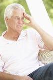 Deprimierter älterer Mann, der im Stuhl sitzt Stockfotografie