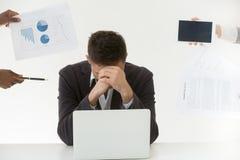 Deprimierter männlicher Angestellter ermüdete durch übermäßige Arbeitsbelastung und Kunden stockfotografie