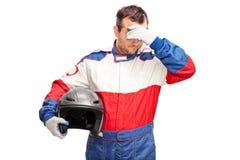 Deprimierter männlicher Autorennläufer, der einen Sturzhelm hält Stockfotografie