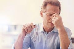 Deprimierter männlicher Büroangestellter, der aheadache hat Stockfotografie