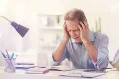 Deprimierter männlicher Büroangestellter, der Kopfschmerzen hat Lizenzfreies Stockbild