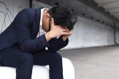 Deprimierter müder junger asiatischer Geschäftsmann in der Klagenbiegung gehen unten voran Stockfoto