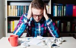 Deprimierter müder Mann, der seinen Kopf hält Lizenzfreies Stockbild