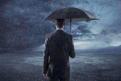 Deprimierter Manager, der mit einem Regenschirm steht Lizenzfreies Stockbild