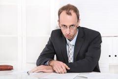 Deprimierter Manager mit der Krise, die am Schreibtisch sitzt. Stockfoto