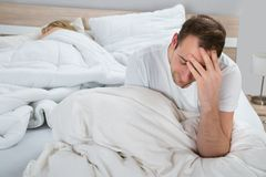 Deprimierter Mann auf Bett während Frauenschlafen Lizenzfreies Stockbild
