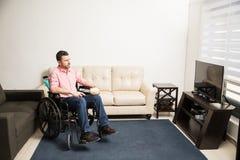 Deprimierter Mann auf einem Rollstuhl zu Hause Stockfoto