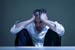 Deprimierter Mann bei der Arbeit Stockbild