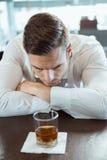Deprimierter Mann, der Alkoholglas betrachtet Stockbilder