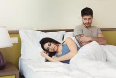 Deprimierter Mann, der auf Bett während Frauenschlafen sitzt Stockfotos