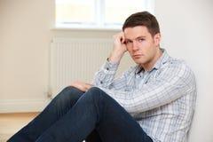 Deprimierter Mann, der auf Boden im leeren Raum sitzt Lizenzfreies Stockfoto