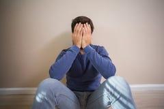 Deprimierter Mann, der auf Boden sitzt Stockfoto