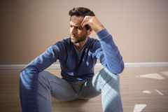 Deprimierter Mann, der auf Boden sitzt Stockfotografie