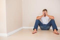 Deprimierter Mann, der auf Boden sitzt Lizenzfreie Stockfotografie