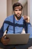 Deprimierter Mann, der auf Boden unter Verwendung des Laptops sitzt Lizenzfreie Stockfotografie