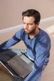 Deprimierter Mann, der auf Boden unter Verwendung des Laptops sitzt Stockfotografie