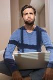 Deprimierter Mann, der auf Boden unter Verwendung des Laptops sitzt Stockfoto