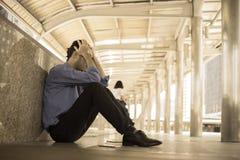 Deprimierter Mann, der auf Bodenkopf in den Händen sitzt Stockbilder