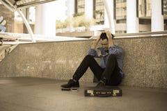 Deprimierter Mann, der auf Bodenkopf in den Händen sitzt Stockfotos