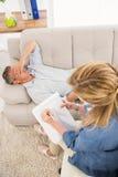 Deprimierter Mann, der auf Couch liegt und mit Therapeuten spricht Lizenzfreies Stockbild