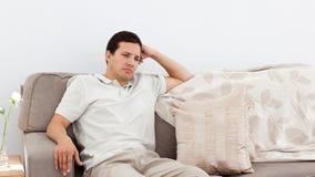 Deprimierter Mann, der auf dem Sofa denkt Stockbild