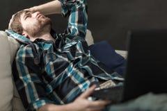 Deprimierter Mann, der auf der Couch sitzt Stockbild