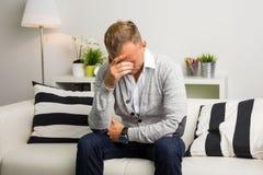 Deprimierter Mann, der auf der Couch sitzt Lizenzfreie Stockfotos