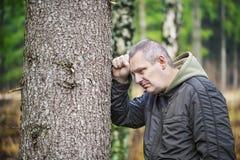 Deprimierter Mann, der auf einem Baum sich lehnt Stockbild